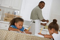 Father watching daughters do homework at kitchen table