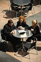 High angle view of businesspeople using laptop at outdoor cafe