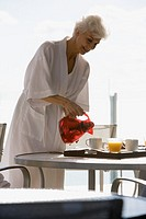 Woman in bathrobe pouring orange juice