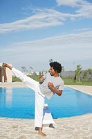 Man practicing martial arts by swimming pool