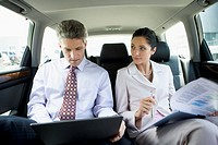 Businesspeople working in backseat of vehicle
