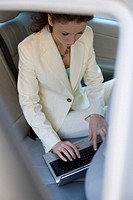 Mirror´s reflection of businesswoman using laptop in backseat of vehicle