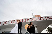 Low angle view of a bride and groom standing with a mature man at a drive-thru wedding chapel