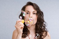 portrait of young woman blowing soap bubbles