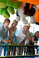 Senior couple and a young couple playing an amusement park game