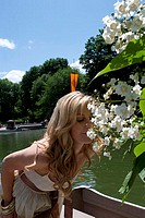 Young woman smelling flowers, Central Park, Manhattan, New York City, New York, USA