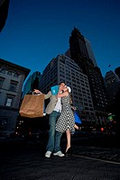 Low angle view of a young woman kissing a young man on the road, New York City, New York, USA