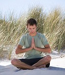 Young man performing yoga on a beach