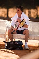 Male tennis player resting