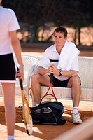 Male tennis player watching female colleague