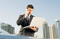 A businessman talkingon a mobile phone holding a laptop