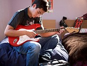 A teenage boy with a guitar