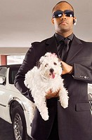 A chauffer holding his boss's pet dog
