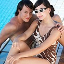 A young couple sitting by a swimming pool