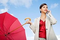 A businesswoman standing underneath an umbrella on a mobile phone