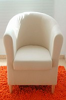 White armchair on orange carpet