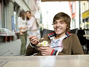 Young man in ice cream parlour, girls watching in background