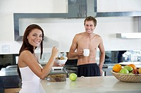 Young couple in kitchen, having breakfast