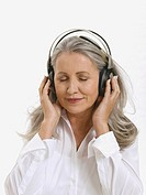 Senior woman wearing headphones, portrait