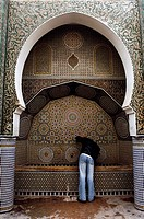 Rear view of a man drinking water from a water fountain in a mosque