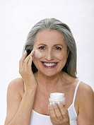 Senior woman applying face cream, portrait