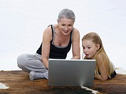 Grandmother and granddaughter using laptop, portrait (thumbnail)