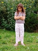 Little girl in garden, pouting