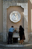 Rear view of a man and a woman standing in front of a faucet, Cascia, Umbria, Italy