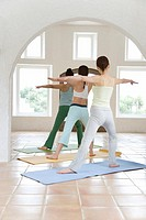 Three Young Women Practicing Yoga, Spreading Arms Out, Rear View