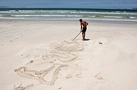 Rear view of a boy drawing in sand with a stick on the beach, Muizenberg Zonwabe Beach, Muizenberg, False Bay, Cape Town, Western Cape Province, South...