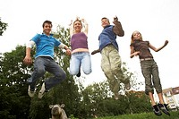 Teenage boys and girls jumping in a park