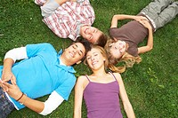 Teenagers lying down on the grass