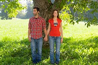 A couple leaning against a tree