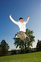 A teenage boy jumping in the air