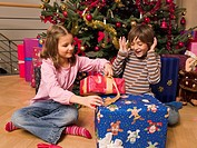 Siblings opening their Christmas presents