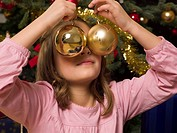 Girl covering eyes with Christmas decorations