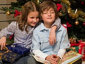 Siblings sitting in front of a Christmas tree