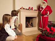 Man dressed as Santa Claus talking to children