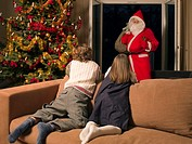 Children watch the man dressed as Santa