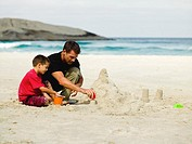 Father and son building sand castles on the beach
