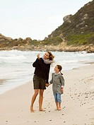 Mother and daughter collecting sea shells on the beach