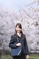 Portrait of a woman standing in the field of cherry blossoms, smiling and looking at camera, front view, Japan