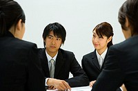 Four young business people in meeting, front view, rear view, white background