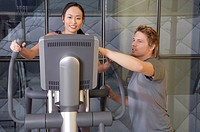 Man helping a woman in the gym