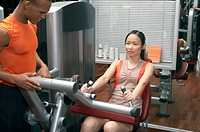 Trainer helping a woman in the gym