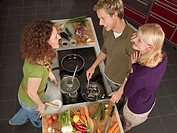 High angle view of a young man and two young women preparing food in the kitchen