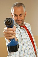 Portrait of a mid adult man holding a drill like a handgun