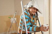 Portrait of a young woman leaning on a step ladder and holding a coffee cup