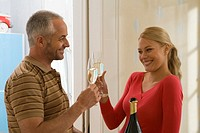 Couple toasting champagne flutes and smiling