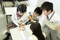 High school students sitting at desk and looking at mobile phone in classroom